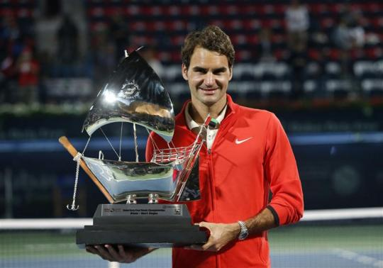 Roger Federer of Switzerland holds trophy after defeating Tomas Berdych of Czech Republic in men's singles final match at ATP Dubai Tennis Championships