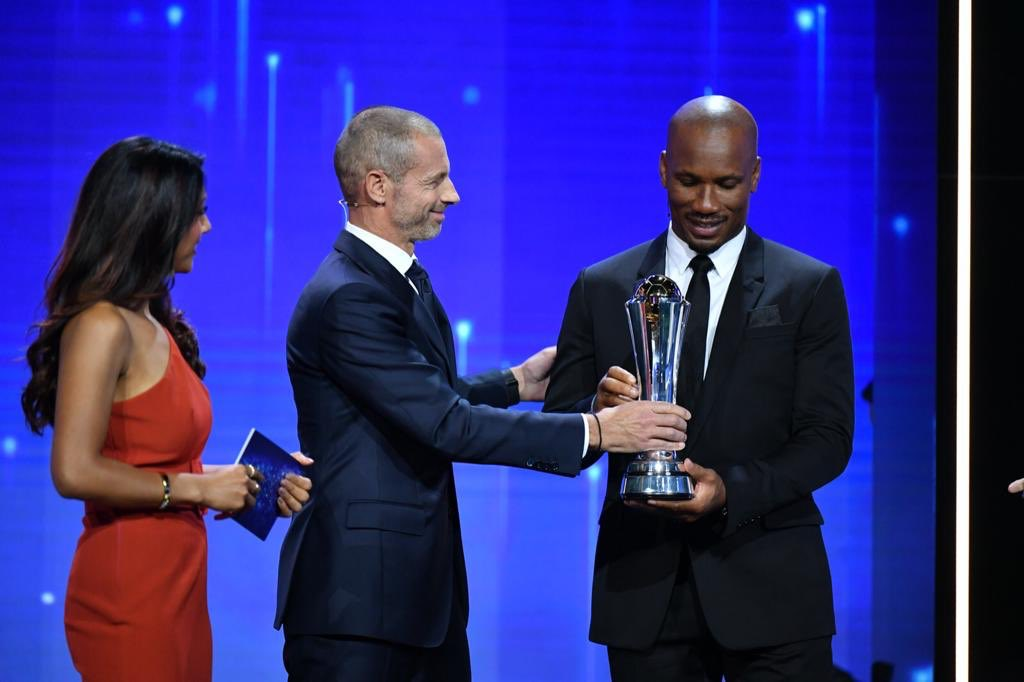 Didier Drogba receiving his award from Aleksander Ceferin's hands.