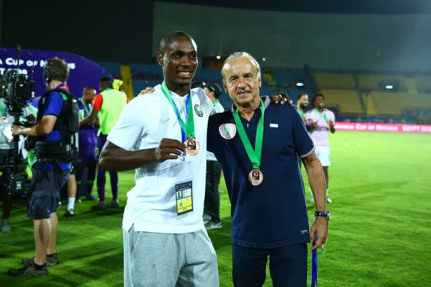 Odion Ighalo wearing the AFCON 2019 Bronze medal alongside Gernot Rohr.