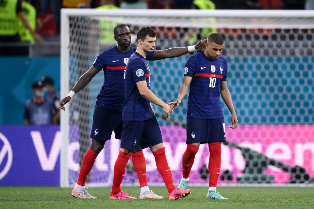 Kylian Mbappé being consoled by his teammates.